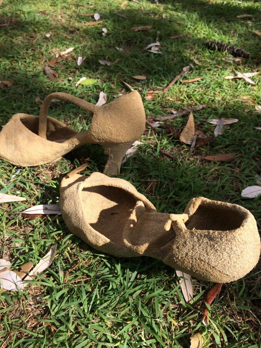 Sandy shoe sculptures brighten my beach walk